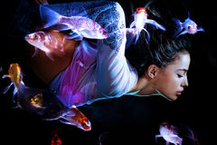 Fantasy woman diving with fishes. Fantasy woman swimming with fishes stock images