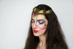 Fantasy woman make up. New creative make-up, conceptual idea for ethnic party. Brunette. Red blue green color graphic shapes, cosmetics shadows paints lines Royalty Free Stock Photos