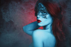Fantasy woman with mask. Fantasy beautiful young woman with lace mask, blue skin and red hair in haze royalty free stock photography