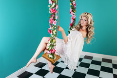 Fantasy Woman on Swing. Surreal, fantasy pinup image of a beautiful woman, on a flower covered swing in an empty room Royalty Free Stock Image