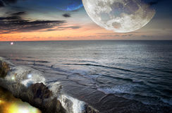 Fantasy world. An imaginary world, with the moon and a planet similar to Earth in the sky, and an ocean of which water falls into another universe Stock Photo