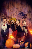 Fantasy world. Cheerful children in halloween costumes celebrating halloween in a wooden barn with pumpkins. Halloween concept stock photo
