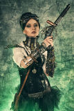 Fantasy world. Portrait of a beautiful steampunk woman holding a gun over grunge background royalty free stock photos