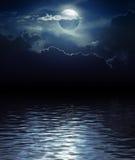 Fantazj chmury nad wodą i księżyc Obrazy Royalty Free