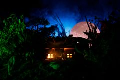 Fantazja dekorująca fotografia Mały piękny dom w trawie z światłem Stary dom w lesie przy nocą z księżyc Selekcyjna ostrość Zdjęcie Stock