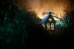 Fantazja dekorująca fotografia Mały piękny dom w trawie z światłem Stary dom w lesie przy nocą z księżyc Selekcyjna ostrość Obrazy Stock