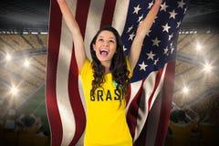 Fanático del fútbol emocionado en la camiseta del Brasil que sostiene la bandera de los E.E.U.U. Foto de archivo libre de regalías