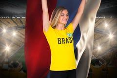 Fanático del fútbol emocionado en la camiseta del Brasil que sostiene la bandera de Rusia Imágenes de archivo libres de regalías