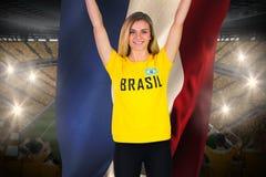 Fanático del fútbol emocionado en la camiseta del Brasil que sostiene la bandera holandesa Imagen de archivo libre de regalías
