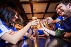 Fanáticos del fútbol que tintinean los vidrios de cerveza en la barra o el pub Foto de archivo
