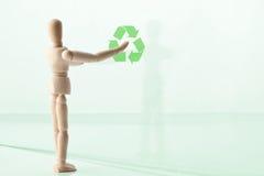 Fantoche de madeira com símbolo de reciclagem verde Foto de Stock
