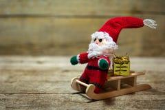 Fantoche de Santa em um pequeno trenó de madeira Imagens de Stock Royalty Free