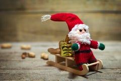 Fantoche de Santa em um pequeno trenó de madeira Fotos de Stock Royalty Free