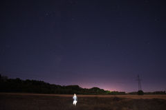 Fantomen av männen visades i fältet precis för gryning mörker I det elektriska tornet för bakgrund med trådar Royaltyfri Foto