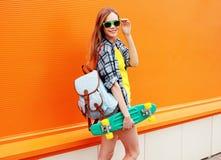 Façonnez à hippie de sourire heureux la fille fraîche dans des lunettes de soleil avec le patin Photographie stock libre de droits