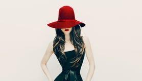 Façonnez la dame de brune dans le chapeau rouge et des lèvres rouges sur le backgroun blanc Photo stock