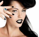 Façonnez la femme avec les clous et les lèvres noirs dans la couleur noire Photos libres de droits