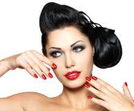 Façonnez la femme avec les languettes rouges, les clous et la coiffure créative Images stock