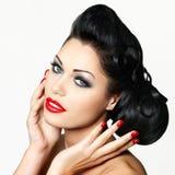 Façonnez la femme avec les languettes rouges, les clous et la coiffure créative Photos stock