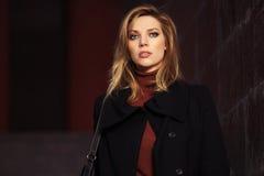 Façonnez la femme blonde dans le manteau noir marchant sur la rue de ville de nuit Images stock