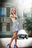 Façonnez la fille avec la jupe courte, le sac et les talons hauts marchant sur la rue Image stock