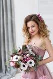Façonnez la photo de studio de la belle jeune fille avec de longs cheveux bouclés en robe rose et fleurs Image stock