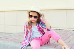 Façonnez le modèle de petite fille utilisant une chemise, un chapeau et des lunettes de soleil roses à carreaux Photographie stock libre de droits