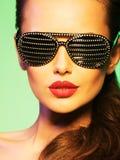Façonnez le portrait de la femme utilisant les lunettes de soleil noires avec le diamant Photos stock