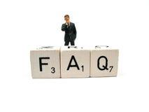 FAQ. A man behind the word FAQ Royalty Free Stock Photography