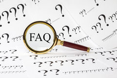 FAQ Concept. A conceptual look at FAQ, frequently asked questions. A magnifyimg glass over the letters FAQ, and a question mark covered background royalty free stock photography