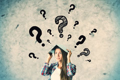 FAQ concept. Pretty caucasian girl with question marks on concrete wall background. FAQ concept stock image