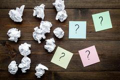 FAQ concept. Question mark on sticky notes near crumpled paper on dark wooden background top view royalty free stock images