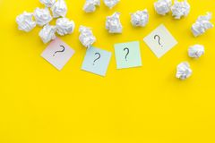 FAQ concept. Question mark on sticky notes near crumpled paper on yellow background top view copy space stock image
