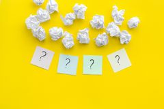 FAQ concept. Question mark on sticky notes near crumpled paper on yellow background top view copy space stock photo