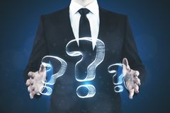 FAQ and confusion concept. Businessman holding abstract drawn question marks on blue background. FAQ and confusion concept Royalty Free Stock Image