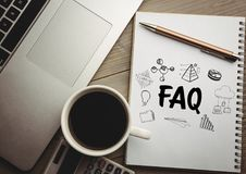 FAQ doodle on notepad next to coffee and laptop royalty free stock image