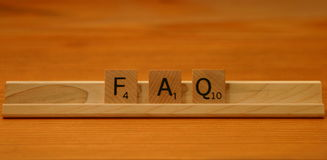 FAQ Fequently Asked Questions. Three Scrabble letters symbolizing Frequently Asked Questions Royalty Free Stock Photography