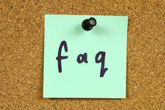 FAQ - Frequently Asked Questions. Green small sticky note on an office cork bulletin board. Internet concept - FAQ acronym, stands for Frequently Asked Questions royalty free stock photography