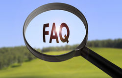 FAQ frequently asked questions. Magnifying glass with the word FAQ frequently asked questions on blurred nature background Royalty Free Stock Photos
