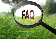 FAQ frequently asked questions. Magnifying glass with the word FAQ frequently asked questions on grass background. Selective focus royalty free stock images