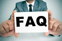 FAQ, Frequently Asked Questions. A man wearing a suit sitting in a desk holding a signboard with the word FAQ, Frequently Asked Questions, written in it royalty free stock photos