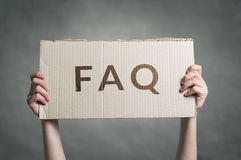 FAQ - Frequently Asked Questions text. On cardboard held Royalty Free Stock Photo