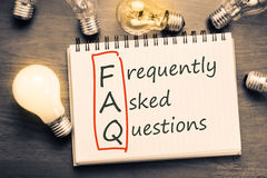 FAQ. ( frequently asked questions ) text on notebook with many light bulbs Stock Photography