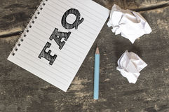 FAQ - Frequently Asked Questions text on a notebook. FAQ - Frequently Asked Questions text on a notebook with pen crumpled paper on wooden table Stock Photography