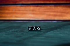 FAQ op houten blokken Kruis verwerkt beeld met bokehachtergrond stock foto