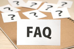 FAQ on a piece of paper and many question marks on notebook. Royalty Free Stock Photo