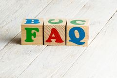 FAQ sign. Colorful wooden blocks on a white wooden background stock photo