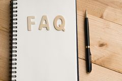 FAQ word with Black pen and book paper. Question and answer concept royalty free stock image