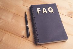 FAQ word with Black pen and book paper. Question and answer concept royalty free stock photo