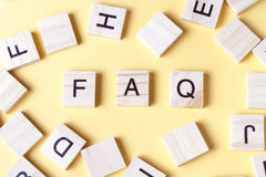 FAQ-Wort geschrieben auf hölzernen Block Hölzernes ABC Lizenzfreies Stockfoto